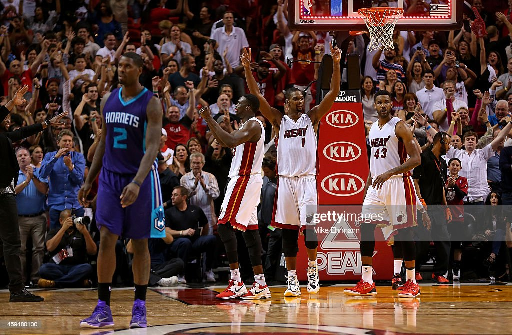 Chris Bosh #1, Luol Deng #9 and Shawne Williams #43 of the Miami Heat react to winning a game against the Charlotte Hornets at American Airlines Arena on November 23, 2014 in Miami, Florida.