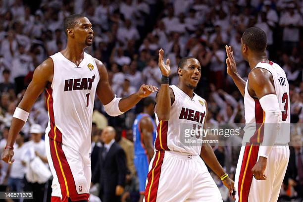 Chris Bosh Mario Chalmers and Dwyane Wade of the Miami Heat celebrate in the fourth quarter against the Oklahoma City Thunder in Game Four of the...