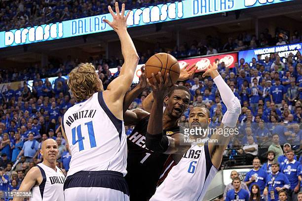 Chris Bosh of the Miami Heat drives for a shot attempt against Dirk Nowitzki and Tyson Chandler of the Dallas Mavericks in Game Five of the 2011 NBA...