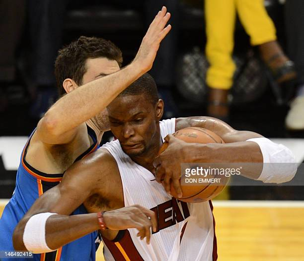 Chris Bosh of the Miami Heat drives past Nick Collison of the Oklahoma City Thunder during Game 3 of the NBA Finals on June 17 2012 at the American...