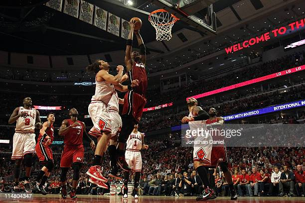 Chris Bosh of the Miami Heat dunks against Joakim Noah and Carlos Boozer of the Chicago Bulls in Game Five of the Eastern Conference Finals during...