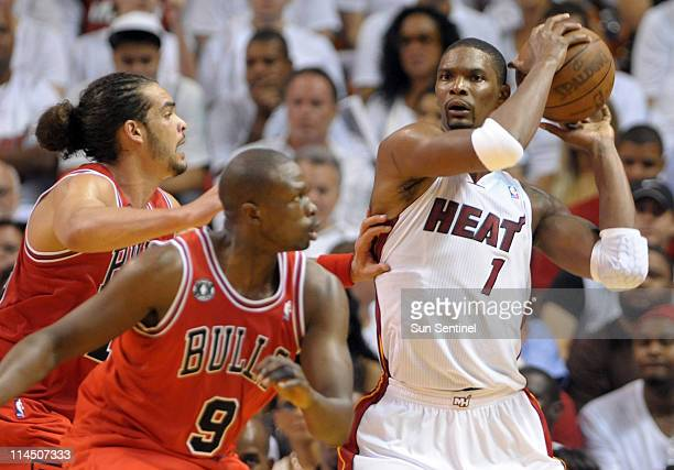 Chris Bosh of the Miami Heat fends off Joakim Noah and Luol Deng of the Chicago Bulls in the third quarter during Game 3 of the NBA Eastern...