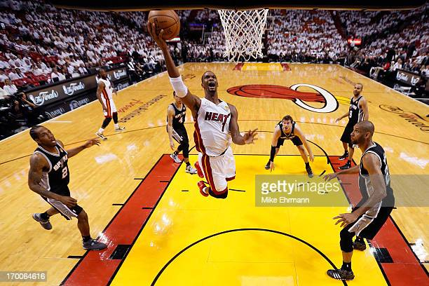 Chris Bosh of the Miami Heat goes up for a shot in the lane between Kawhi Leonard and Tim Duncan of the San Antonio Spurs in the third quarter during...