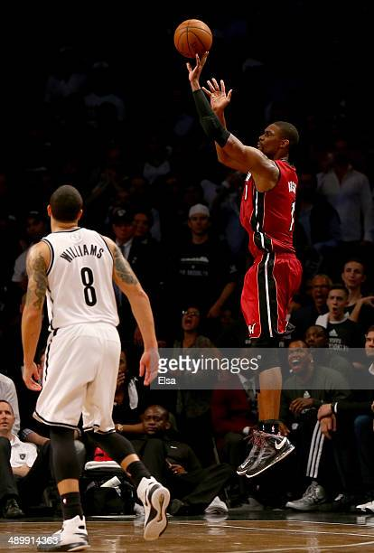 Chris Bosh of the Miami Heat shoots a three point shot in the final minutes of the game as Deron Williams of the Brooklyn Nets defends in Game Four...