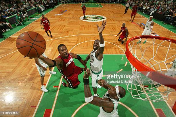 Chris Bosh of the Miami Heat shoots against Kevin Garnett and Jermaine O'Neal of the Boston Celtics during Game Three of the Eastern Conference...