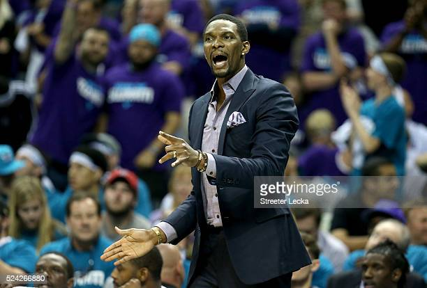 Chris Bosh of the Miami Heat watches on from the bench against the Charlotte Hornets during game four of the Eastern Conference Quarterfinals of the...