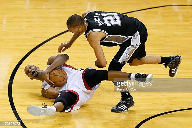 Chris Bosh of the Miami Heat with the ball on the court as Tim Duncan of the San Antonio Spurs goes after it in the first half during Game Six of the...