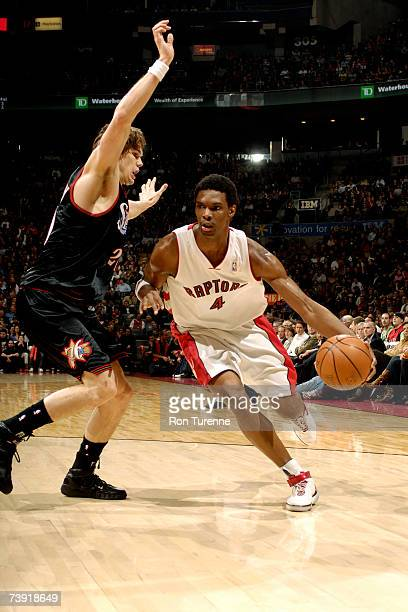 Chris Bosh of the Toronto Raptors drives around Louis Amundson of the Philadelphia 76ers on April 18 2007 at the Air Canada Centre in Toronto Canada...