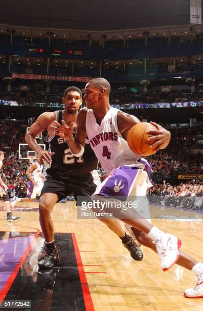 Chris Bosh of the Toronto Raptors drives baseline against Tim Duncan of the San Antonio Spurs on November 21 2004 at the Air Canada Centre in Toronto...