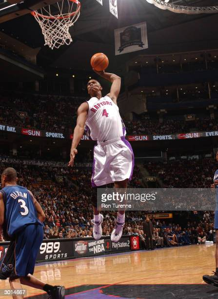 Chris Bosh of the Toronto Raptors drives for a dunk against Juan Dixon of the Washington Wizards on February 25 2004 at the Air Canada Centre in...