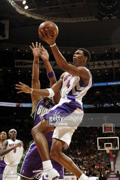 Chris Bosh of the Toronto Raptors drives past Maurice Williams of the Milwaukee Bucks on March 17 2006 at the Air Canada Centre in Toronto Canada...