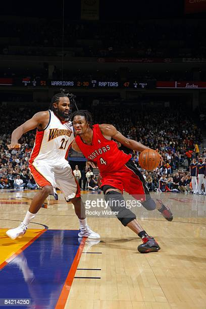 Chris Bosh of the Toronto Raptors drives to the basket against Ronny Turiaf of the Golden State Warriors during the game at Oracle Arena in Oakland...