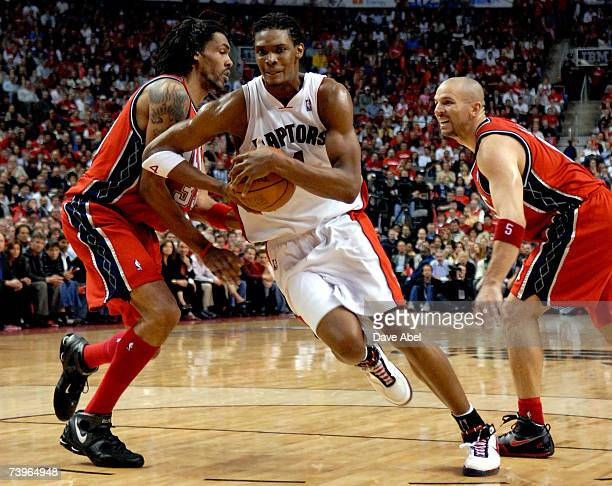 Chris Bosh of the Toronto Raptors gets through defenders Mikki Moore and  Jason Kidd of the. Toronto Raptors v New Jersey Nets ... 74113faf1