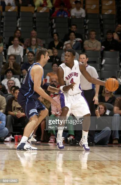 Chris Bosh of the Toronto Raptors look to drive on Mehmet Okur of the Utah Jazz on October 12 2005 at the Air Canada Centre in Toronto Canada The...