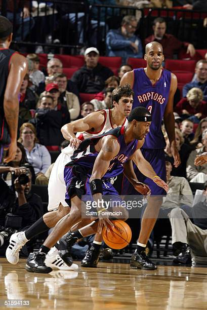 Chris Bosh of the Toronto Raptors takes the ball past Richie Frahm of the Portland Trail Blazers in NBA preseason action October 27 2004 at the Rose...