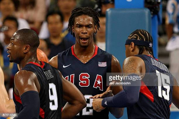 Chris Bosh of the United States reacts between teammates Dwyane Wade and Carmelo Anthony of the United States while taking on Argentina during a...