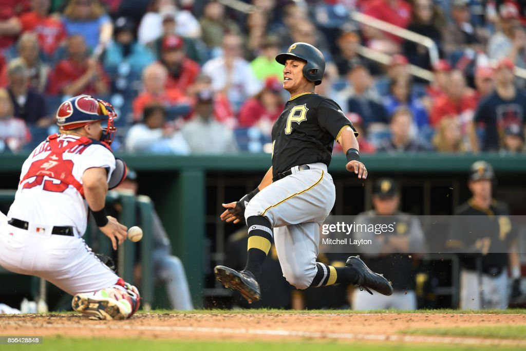 Chris Bostick #63 of the Pittsburgh Pirates beats the tag by Jose Lobaton #59 of the Washington Nationals in the eight inning on a Josh Bell #58 (not pictured) single during a baseball game against the Pittsburgh Pirates at Nationals Park on October 1, 2017 in Washington, DC.