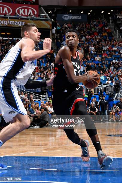 Chris Boucher of the Toronto Raptors drives through the paint during the game against Nikola Vucevic of the Orlando Magic on December 28 2018 at...