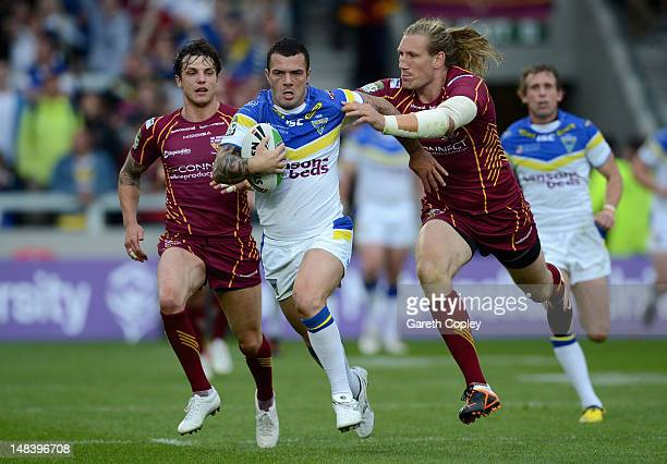 Chris Bridge of Warrington is tackled by Eorl Crabtree of Huddersfield during the Carnegie Challenge Cup Semi Final match between Huddersfield Giants...