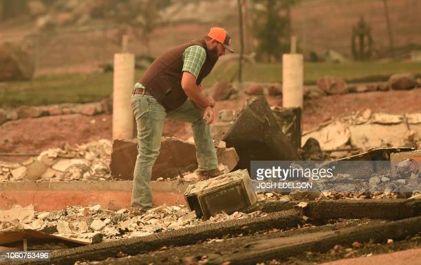 Chris Brown looks over the remains of his burned home in Paradise California on November 12 2018 Thousands of firefighters spent a fifth day digging...