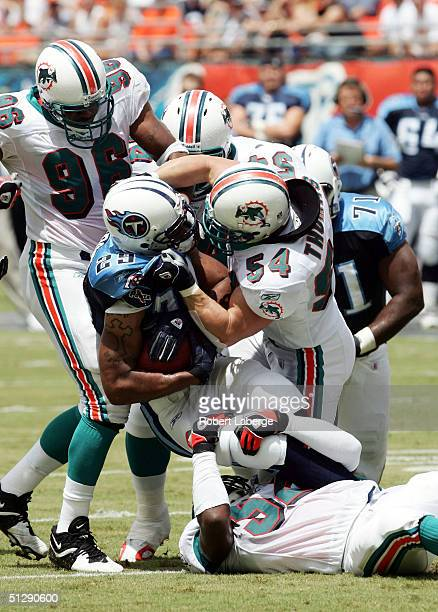 Chris Brown of the Tennessee Titans gets tackled to the ground by Zach Thomas of the Miami Dolphins in the first half of the game won by the Titans...