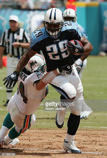 Chris Brown of the Tennessee Titans runs as Zach Thomas of the Miami Dolphins tries to stop him in the first half of the game at Pro Player Stadium...