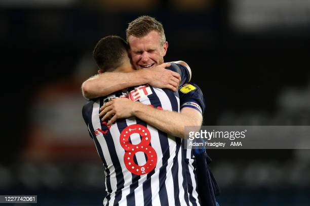 Chris Brunt and Jake Livermore of West Bromwich Albion embrace as they celebrate promotion to the Premier League on the pitch at the end of the Sky...