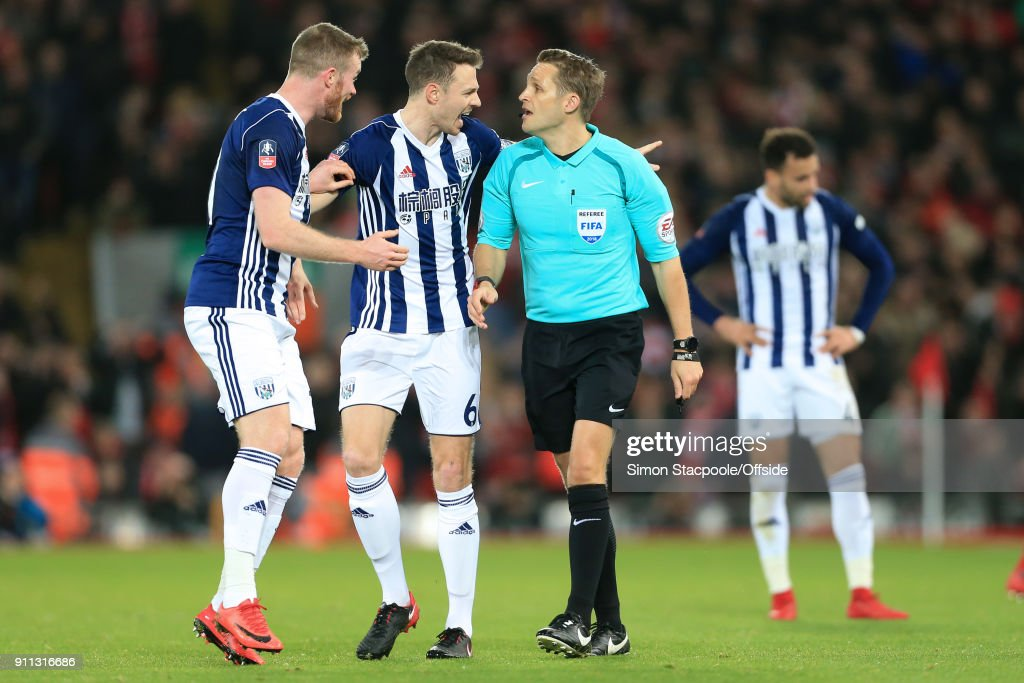 Chris Brunt of West Brom (L) and Jonny Evans of West Brom (C) react after referee Craig Pawson awarded a penalty following a decision to refer to the Video Assistant Referee (VAR) system during The Emirates FA Cup Fourth Round match between Liverpool and West Bromwich Albion at Anfield on January 27, 2018 in Liverpool, England.