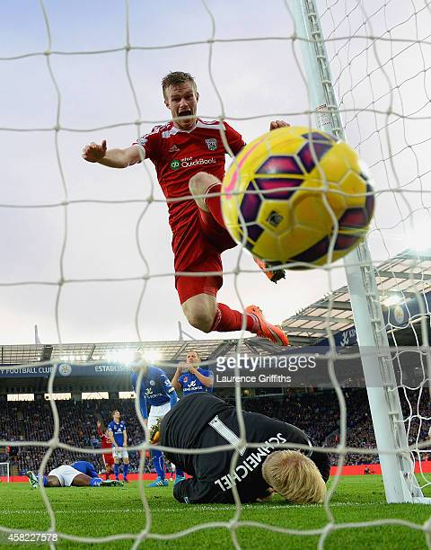 Chris Brunt of West Brom celebrates as he jumps over Kasper Schmeichel of Leicester City after Esteban Cambiasso of Leicester City scored an own goal...