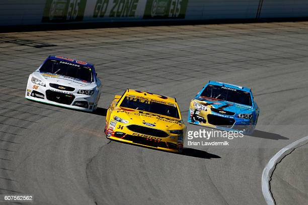 Chris Buescher driver of the Love's Travel Stops Ford leads Reed Sorenson driver of the Vic's Express Car Wash/Vydox Plus Chevrolet and Danica...