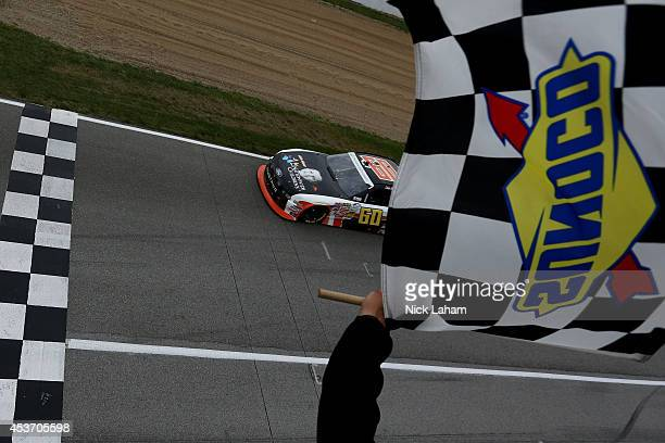 Chris Buescher driver of the Nationwide Children's Hospital Ford Mustang Ford takes the checkered flag to win the Nationwide Children's 200 at...