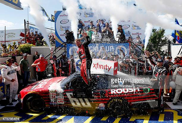 Chris Buescher driver of the Roush Performance Products Ford celebrates in Victory Lane after winning the NASCAR XFINITY Series Buckle Up 200...