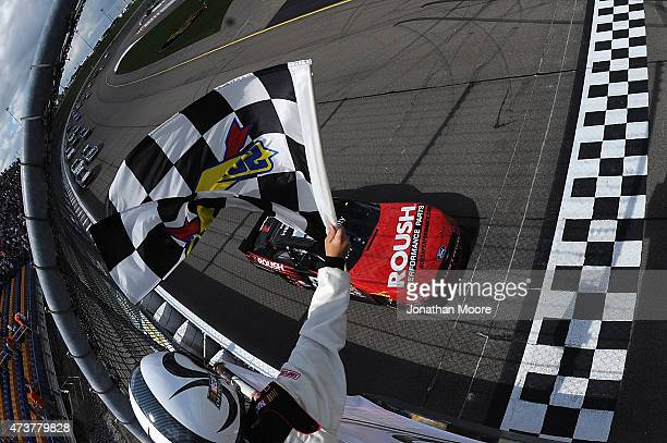 Chris Buescher driver of the Roush Performance Products Ford Mustang Ford takes the checkered flag in the NASCAR XFinity Series 3M 250 at Iowa...