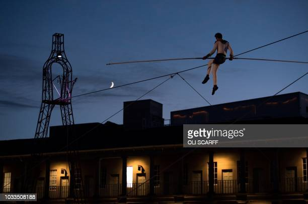 Chris Bullzini a funambulist or highwire artist performs on a tightrope above the courtyard of The Piece Hall in Halifax northern England on...