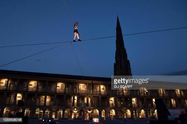 Chris Bullzini, a funambulist or high-wire artist, performs on a tightrope above the courtyard of The Piece Hall in Halifax, northern England on...