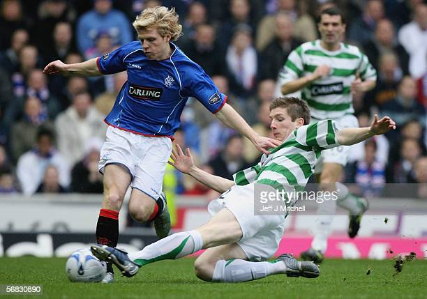 Chris Burke of Rangers is tackled by Mark Wilson of Celtic during the Scottish Premier League match between Rangers and Celtic at Ibrox Stadium on...