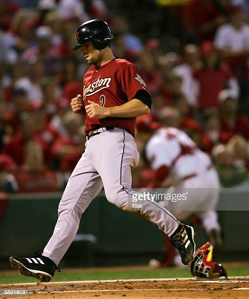 Chris Burke of the Houston Astros score a run on a wild pitch in the second inning against the St Louis Cardinals during Game Two of the National...