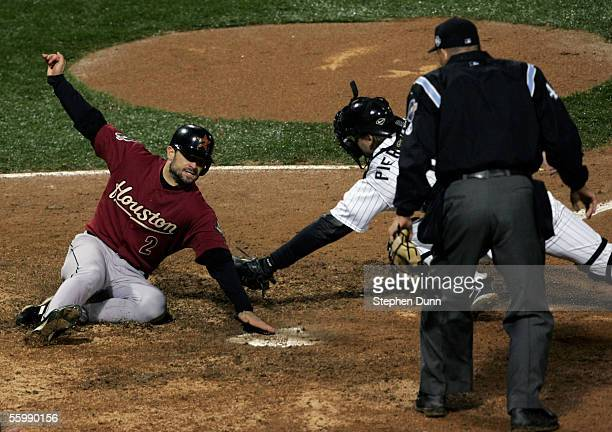 Chris Burke of the Houston Astros slides safely into homeplate past the tag of catcher AJ Pierzynski of the Chicago White Sox as homeplate umpire...