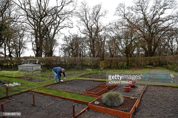 Chris Burrows works to plant seeds at his allotment in Hartley Wintney west of London on March 29 as life in Britain continues during the nationwide...