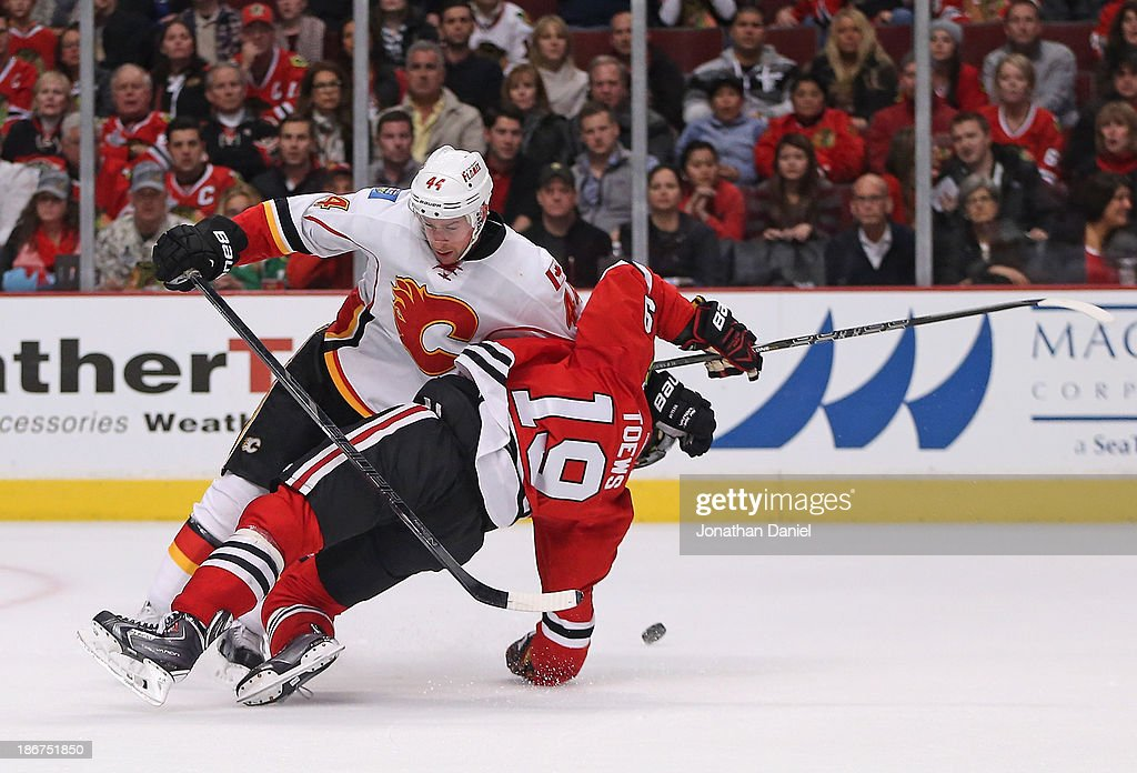 Chris Butler #44 of the Calgary Flames takes down Jonathan Toews #19 of the Chicago Blackhawks for a penalty at the United Center on November 3, 2013 in Chicago, Illinois. The Flames defeated the Blackhawks 3-2 in overtime.