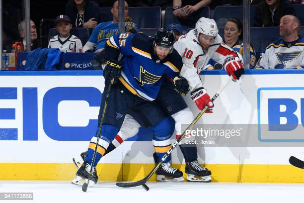 Chris Butler of the St Louis Blues and Brett Connolly of the Washington Capitals battle for the puck at Scottrade Center on April 2 2018 in St Louis...
