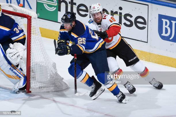 Chris Butler of the St Louis Blues and James Neal of the Calgary Flames battle for the puck at Enterprise Center on December 16 2018 in St Louis...