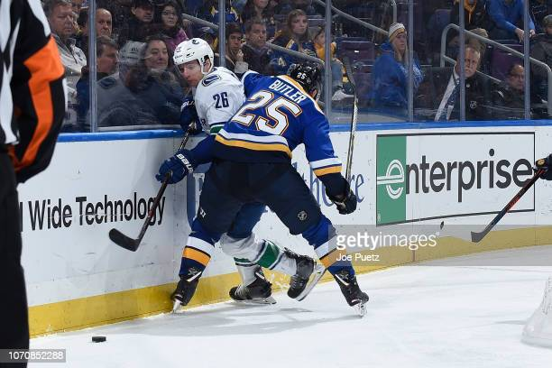 Chris Butler of the St Louis Blues defends against Antoine Roussel of the Vancouver Canucks at Enterprise Center on December 9 2018 in St Louis...