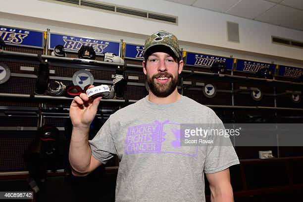 Chris Butler of the St Louis Blues poses for a photograph with the puck from his first career goal while playing against the Colorado Avalanche on...