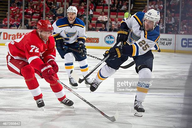 Chris Butler of the St Louis Blues shoots puck past Erik Cole of the Detroit Red Wings during a NHL game on March 22 2015 at Joe Louis Arena in...