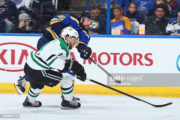 Chris Butler of the St Louis Blues shoots the puck against Jason Demers of the Dallas Stars at the Scottrade Center on December 27 2014 in St Louis...