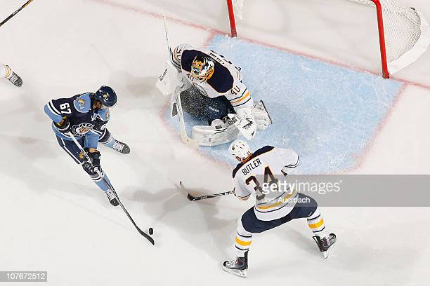 Chris Butler watches as Goaltender Patrick Lalime of the Buffalo Sabres stops a shot by Michael Frolik of the Florida Panthers on December 17, 2010...
