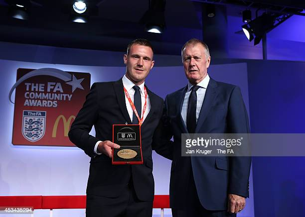 Chris Byrne receives the People's Award for Outstanding Contribution from Sir Geoff Hurst during the FA Community Shield match between Manchester...