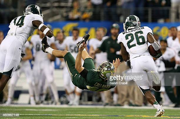 Chris Callahan of the Baylor Bears is blocked by Tony Lippett of the Michigan State Spartans as RJ Williamson of the Michigan State Spartans returns...