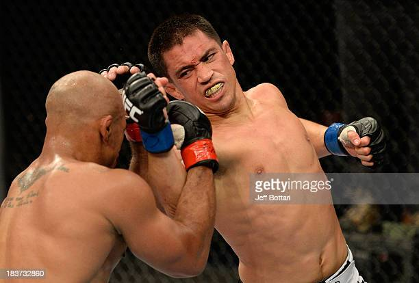 Chris Cariaso punches Iliarde Santos in their flyweight bout during the UFC Fight Night event at the Ginasio Jose Correa on October 9, 2013 in...